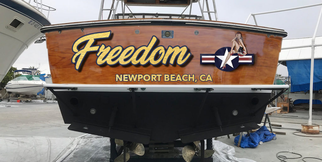 "Faux Teak wood with gold leaf lettering, ""Freedom"" and with a 'pin-up' graphic."